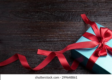 green gift box red bow on wood table, top view