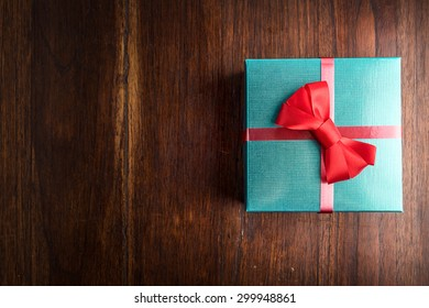 green gift box and red ribbon on wood desk