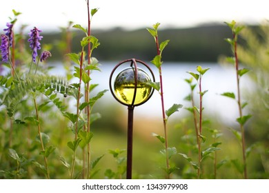 A green glass ball in nature. Summertime in Sweden.