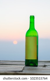 Green glass bottle on the bamboo table with natural background and sun light