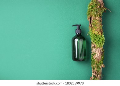 Green glass bottle of shampoo, soap, conditioner on green background with natural moss over bark, wood. Top view, copy space. Blank label for mock-up. Skin care, organic body treatment, spa concept.