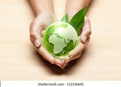 Un globe de verre vert entre les mains