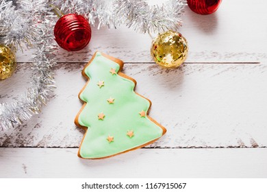 A green glaze Christmas gingerbread cookie in the shape of Chrismas tree on a wooden table. Close-up, selective focus, bokeh, copy space