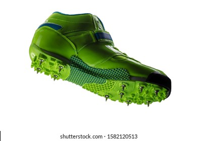 Green glossy sneaker with spikes on a white background. Sport shoes.