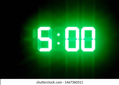 Green glowing digital clocks in the dark show 5:00 time