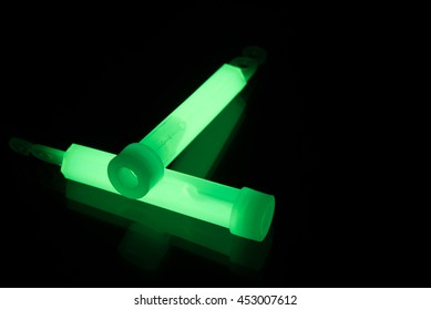 Green glowsticks on a reflective surface