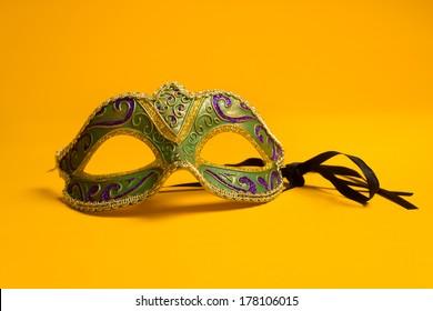 Green, gold, purple mardi gras mask on a bright yellow background