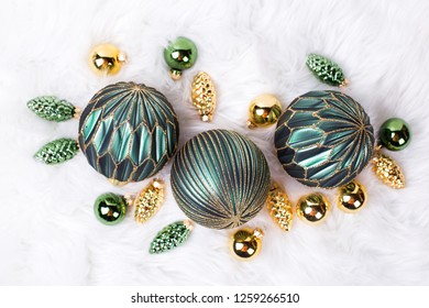 Green and golden balls, golden pine cones, fairy lights  on white fur white background. Decorative christmas composition. Selective focus.  Place for text. Top view.