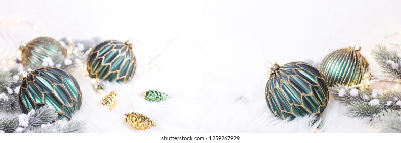 Green and golden balls, golden pine cones, fairy lights  and fir tree branches  on white fur white background. Selective focus. Long banner formate. Site header. Place for text.