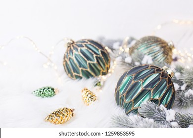 Green and golden balls, golden pine cones, fairy lights  and fir tree branches  on white fur white background. Decorative christmas composition. Selective focus.  Place for text.