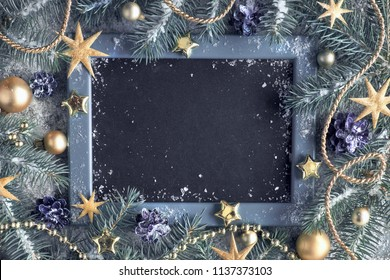 Green and golden Christmas background. Decorated fir twigs around chalk board on rustic wood with snow. Top view with copy space.