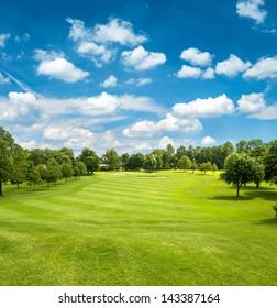 green golf field and blue cloudy sky. european landscape