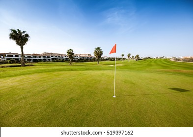 Green golf field with red flag in sunlight
