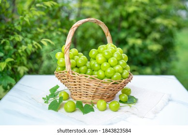 Green grape in Bamboo basket on white marble table in garden, Shine Muscat Grape with leaves in blur background.