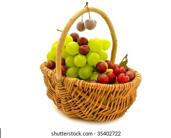 green grape and red cherry in hand-made basket against white background