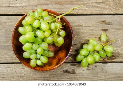 Green grapes. A branch of white grapes in wooden bowl on a wooden table