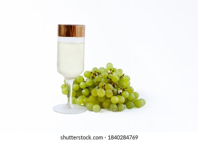 Green grapes with a glass of grape juice or wine on a white background