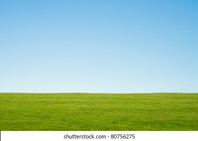 Green grass and blue sky landscape background, providing copy space in the sky.  Horizontal orientation.