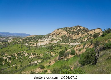 Green grass and brush cover a hillside in southern California near Santa Clarita