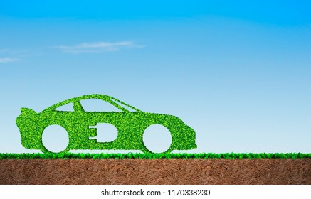 Green grass in car shape, on blue sky and soil cross section background, concept of ECO, renewable energy and circular economy