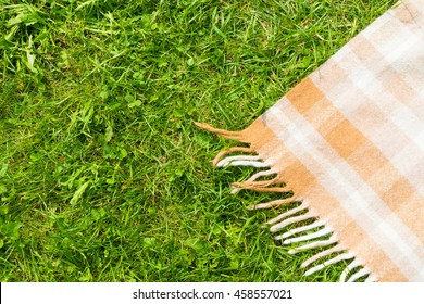 Green grass and checkered beige tablecloth background for picnic, top view