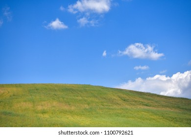 Green grass covered hill and blue sky with puffy clouds. Springtime in Sicily