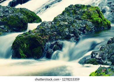 Green grass covered with ice at the creek. Boiling and rumbling cascading waterfall.