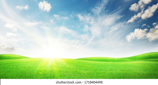 Green grass field and blue sky with bright sun summer landscape background