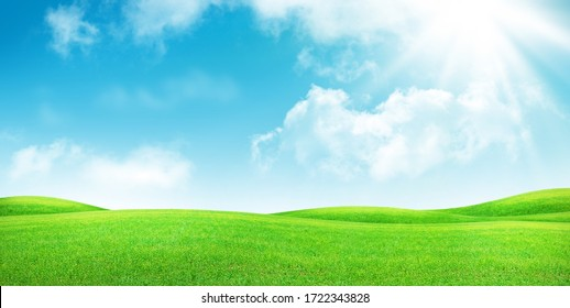 Grünes Grasfeld und blauer Himmel mit heller Sonnenlandschaft