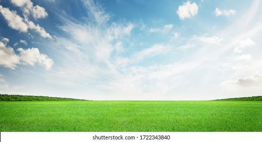 Green grass field and blue sky summer landscape background - Shutterstock ID 1722343840
