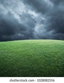 Green grass field with dark storm clouds before rain