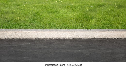 Green Grass Grows Near Black Asphalt, Separated By Concrete Border. Road And Lawn Divided By Concrete Curb.