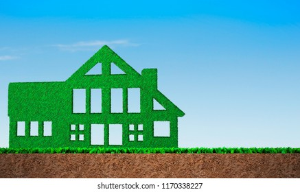Green grass in house shape, on blue sky and soil cross section background, concept of ECO, renewable energy and circular economy.