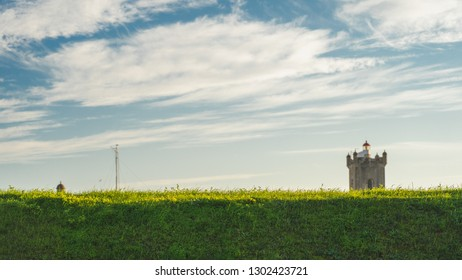 Green grass in the land in front of the lighthouse tower of Saint Julian Fortress Oeiras, Lisbon