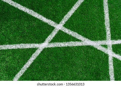 green grass on the football field with white non-parallel stripes on it