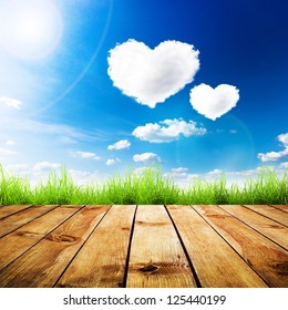 Green grass on wooden plank over a blue sky with hearts shape clouds. Beauty natural background