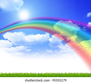 Green grass over a blue sky background with rainbow