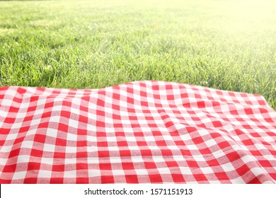 Green grass red checked picnic cloth blanket top view background.Food advertisement design backdrop.