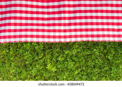 Green grass and red checkered tablecloth background for picnic, top view
