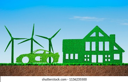 Green grass in shape of wind turbines, electric car and building, on blue sky and meadow soil cross section background, concept of ECO, renewable energy and circular economy.
