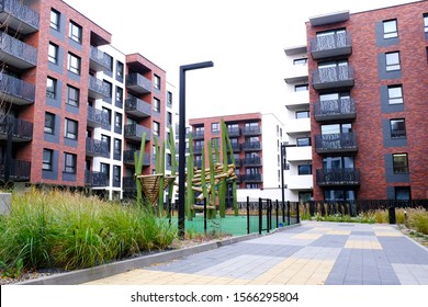 Green grass, sidewalk, wooden playground for children in a cozy courtyard of modern residential buildings district. No people. Real Estate Business concept