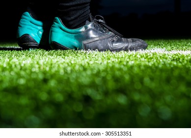 green grass soccer field with foot of soccer player