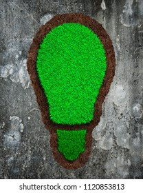 Green grass and soil in the shape of light bulb, on mottled concrete wall background, concept of ECO and renewable energy.