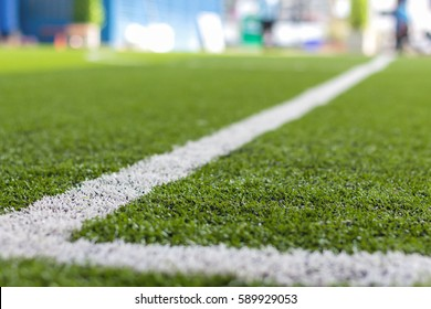 Green grass and sport lines painted at an outdoor playing field (artificial covering)