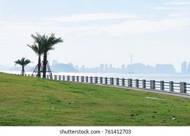 Green grass with stone handrail at seaside, Xiamen Bay Park, China