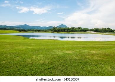 Green grass yard with lake, Thailand.