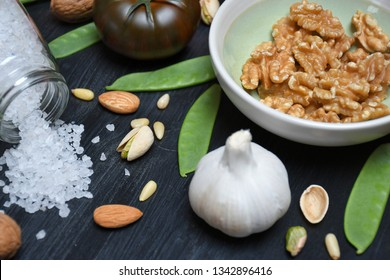 A green and gray bowl with walnuts, a tomato, a garlic, several pine nuts, pistachios, almonds, a few pea pods nearby and a glass jar with spilled Persian blue salt lying on a black wooden surface
