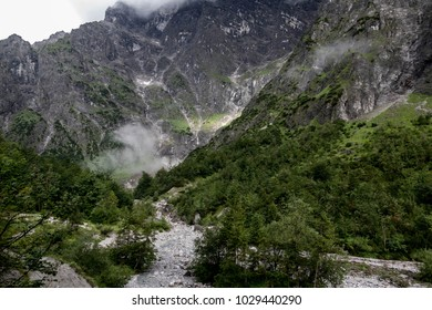 Green and Grey Mountain Side with Clouds and Fog