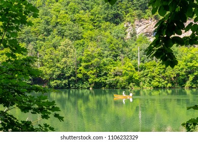 Green Hamori lake in Lillafured near Miskolc, Hungary. Springtime landscape in Beech Mountains with unrecognisable people on boat