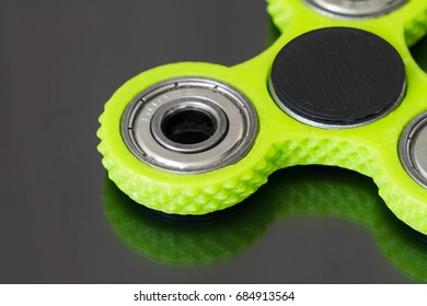 A green hand spinner or fidget spinner on dark mirror surface. A toy for stress relieving. Close up. Selective focus.
